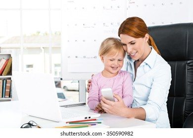 Portrait of cute little girl and her mother while working day. Business woman trying to amuse her daughter. Girl using mobile phone