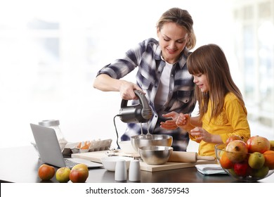 Portrait of cute little girl and her daughter baking cookies together at home.