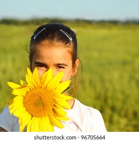 Portrait of a cute little girl hiding behind sunflower on sunny day