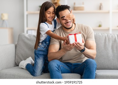 Portrait of cute little girl holding and giving wrapped gift box, making surprise for her excited dad, covering his eyes, greeting young man with father's day or birthday, celebrating at home