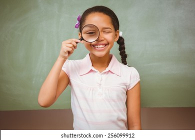 Portrait of cute little girl holding magnifying glass in the classroom