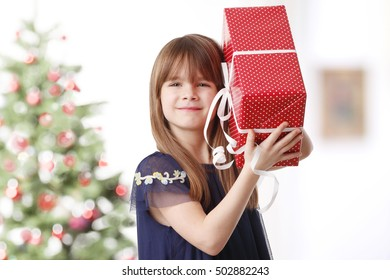 Portrait of cute little girl holding in hand her christmas gift while standing at home in front of christmas tree.
