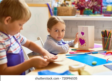 Portrait of cute little girl holding handmade gift card for mom and looking at camera while sitting at desk during art class in pre-school