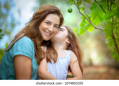Portrait of a cute little girl kissing her mother, happy family with pleasure spending time together in the fruits garden, enjoying spring nature and gentle feelings