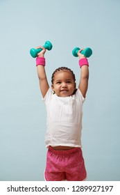 Portrait of cute little girl lifting small colored dumbbells overhead against pale blue background. Pink shorts and wristbands. Fitness workout. Looking for approval.