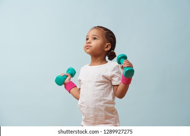 Portrait of cute little girl lifting small colored dumbbells against pale blue background. Pink shorts and wristbands. Fitness workout.