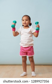 Portrait of cute little girl lifting small colored dumbbells at home. Pink shorts and wristbands. Fitness workout.
