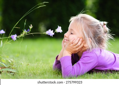 A portrait of a cute little girl lying on the ground in the garden on a nice summer day and  looking at a wild flower