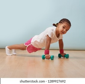 Portrait of cute little girl making push ups on dumbbells at home. Pink shorts and wristbands. Fitness workout.