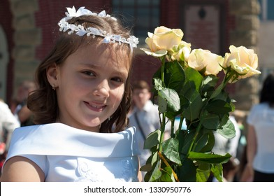 Portrait of cute little girl on white dress and wreath of first holy communion