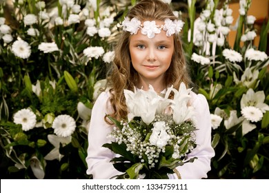 Portrait of cute little girl on white dress and wreath on first holy communion background church gate - Image.