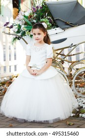 Portrait of cute little girl on awesome white dress on first holy communion