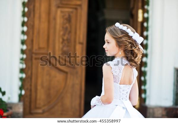 Portret van schattig meisje op witte jurk en krans op eerste heilige communie achtergrond kerkpoort