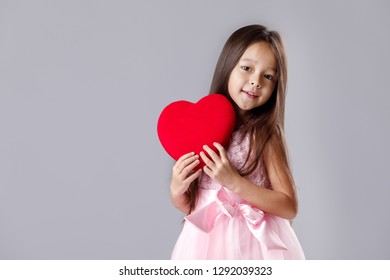 19735bdcf292 portrait of a cute little girl in a pink dress holding a paper heart on gray