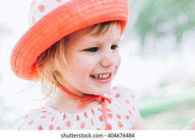 portrait of a cute little girl in a pink red bonnet outdoors smiling