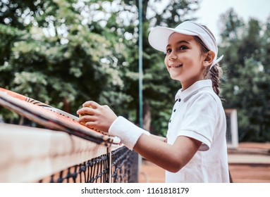 Portrait of cute little girl playing tennis. Child in sport wear hold racket and ball leaning on a tennis net.