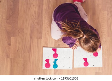 A portrait of cute little girl playing handmade keys  sorting game.Homeschool concept.Education concept.Kids learning background.Toddler handmade game.Kindergarden education.Little girl learning shape