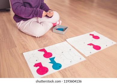 A portrait of cute little girl playing handmade keys  sorting game.Homeschool concept.Education concept.Kid learning background.Toddler handmade game.Kindergarden education.Little girl learning shape.