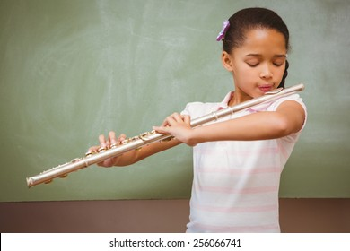 Portrait of cute little girl playing flute in classroom