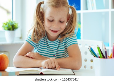 Portrait of a cute little girl read book at the table in light classroom