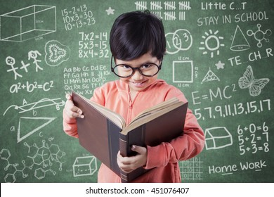 Portrait of a cute little girl reading a book in the class with doodles on the chalkboard