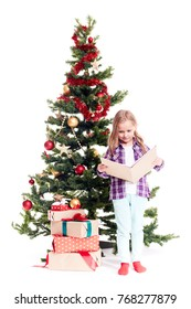 Portrait of cute little girl reading book near Christmas tree on white background