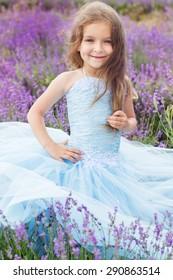 Portrait of cute little girl is resting in a lavender field