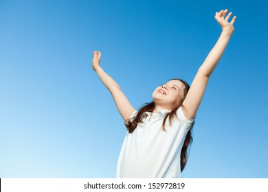 A portrait of a cute little girl, she is standing outside, wearing a white shirt against a blue sky, she has her arms up in the air, she looks very happy.