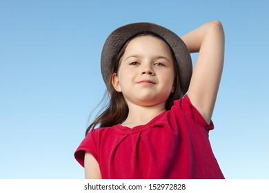 A portrait of a cute little girl, she is standing outside, wearing a hat and a red shirt against a blue sky,