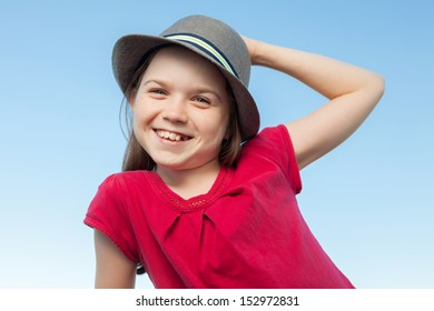 A portrait of a cute little girl, she is standing outside, wearing a hat and a red shirt against a blue sky,she is smiling into the camera