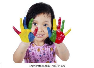 Portrait of a cute little girl showing her hands painted in colorful, isolated on white background