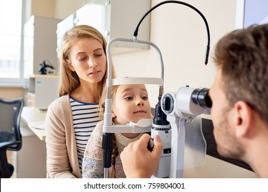 Portrait of cute little girl siting on mothers lap  looking at slit lamp machine during medical check up in eye clinic