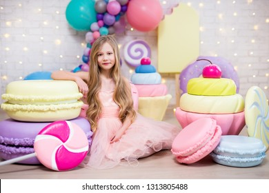portrait of cute little girl sitting with big artificial sweets