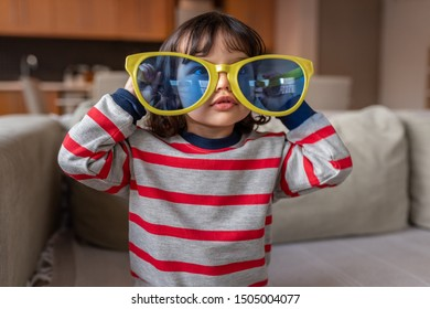 Portrait of a cute little girl sitting in her living room at home wearing funny oversized novelty sunglasses