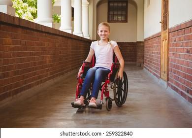 Portrait of cute little girl sitting in wheelchair in school corridor