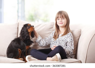 Portrait of cute little girl sitting with her pet on sofa at home and holding digital tablet in her hand.