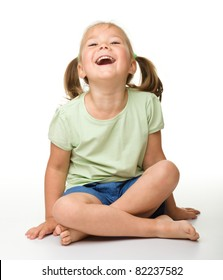 Portrait of a cute little girl sitting on floor, laughing, isolated over white