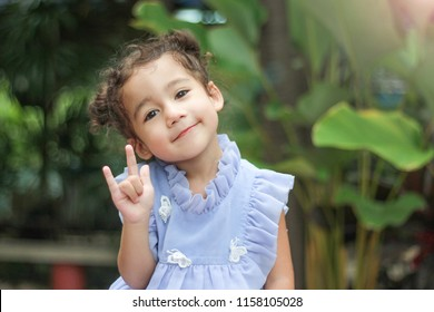 Portrait of a cute little girl smiling with love hand sign. Sign language.