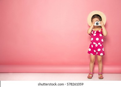 Portrait of cute little girl in straw hat and pink jumpers taking picture with white camera in the studio on pink background. Photography concept. Copy space for text