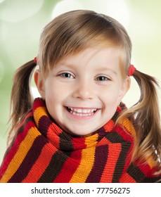 portrait of a cute little girl in a striped scarf