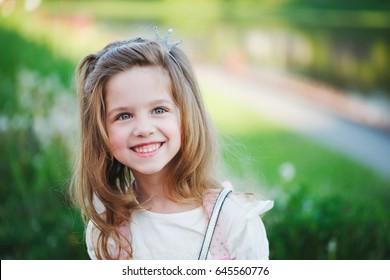portrait of cute little girl in summer park