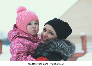 Portrait of a cute little girl walking with her mother on winter street