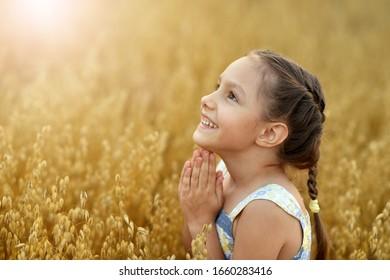 Portrait of cute little girl in wheat field praying