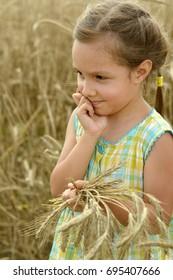 portrait of cute little girl in wheat field