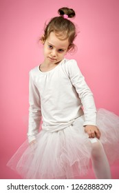 portrait of a cute little girl in white tulle skirt on a pink background