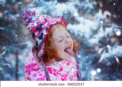 Portrait of a cute little girl who catches snowflakes mouth in winter day.