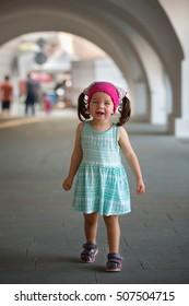 Portrait of cute little girls under the arcades square