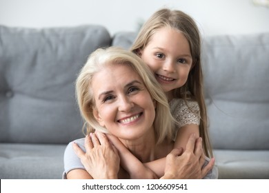 Portrait of cute little granddaughter piggyback smiling grandmother posing for family picture, granny and grandchild hugging having fun together, small girl embrace loving granny spending time at home