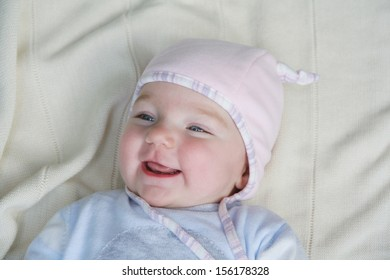 Portrait of cute little happy baby laying on a blanket wearing funny pink hat and knitted blue body