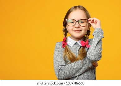 Portrait of a cute little kid girl in glasses on a yellow background. Child schoolgirl looking at the camera. The concept of education. Copy space.